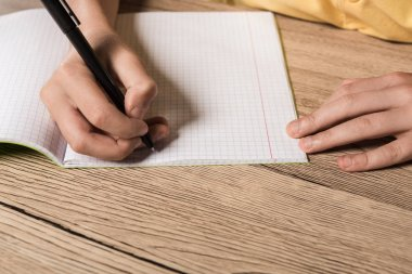 cropped image of schoolboy doing homework in empty textbook at table