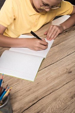 partial view of schoolboy in eyeglasses writing in empty textbook at table with colour pencils