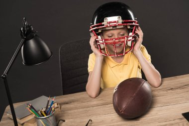 smiling schoolboy putting on american football helmet at table with ball, lamp, colour pencils and books on grey background