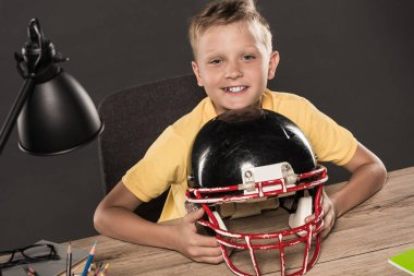 happy schoolboy sitting with american football helmet at table with eyeglasses, lamp, colour pencils and books on grey background