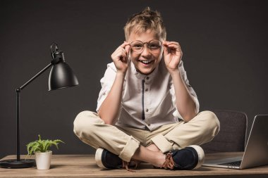 smiling little boy in eyeglasses sitting on table with plant, lamp and laptop on grey background