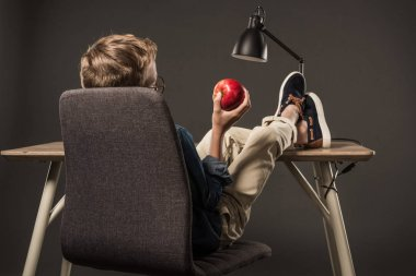 rear view of little boy resting with legs on table and holding apple on grey background