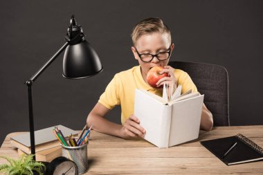 Serious schoolboy in eyeglasses reading book and eating apple at table with colour pencils, clock, lamp, stack of books and textbook on grey background stock vector