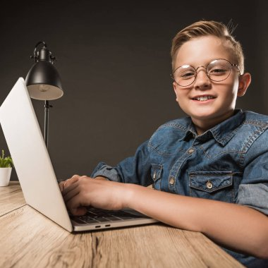 smiling little boy in eyeglasses using laptop at table with lamp and plant on grey background