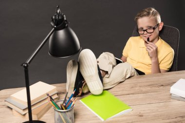 smiling schoolboy in eyeglass doing homework with legs on table with lamp, books, colour pencils and textbook on grey background