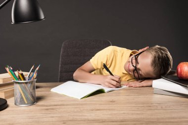 schoolboy in eyeglass laying on table and doing homework at table with lamp, books, colour pencils and textbook on grey background