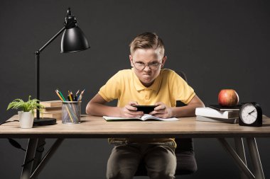 angry schoolboy in eyeglasses using smartphone and sitting at table with books, plant, clock, plant, colour pencils, lamp, textbooks on grey background