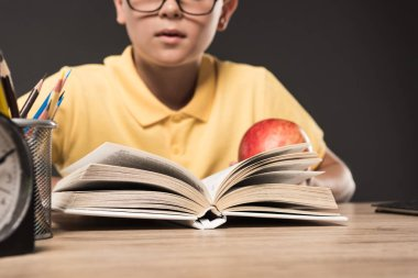cropped image of schoolboy in eyeglasses eating apple and reading book at table with colour pencils and clock on grey background