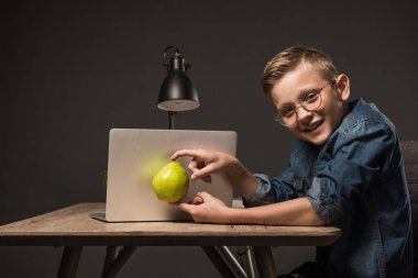 smiling little boy in eyeglasses holding pear in front of laptop at table with laptop on grey background