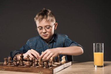 focused little boy playing chess at table with glass of juice on grey background