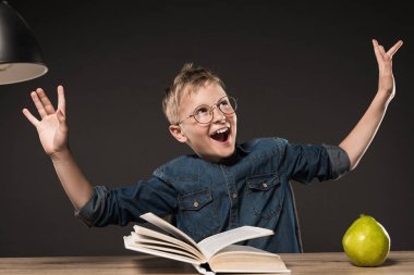 excited school boy in eyeglasses gesturing by hands while reading book at table with lamp and pear on grey background