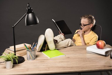 schoolboy in eyeglasses doing homework with legs on table with books, plant, lamp, colour pencils, apple, clock and textbook on grey background