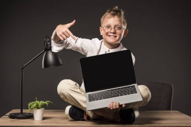 smiling little boy in eyeglasses sitting on table and pointing on laptop with blank screen on grey background