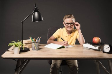 little schoolboy in eyeglasses doing homework at table with books, plant, lamp, colour pencils, apple, clock and textbook on grey background