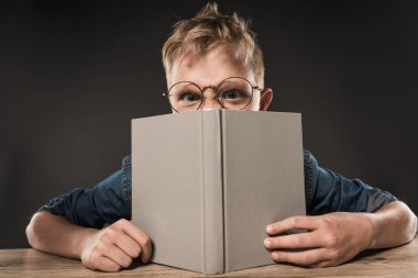 angry schoolboy in eyeglasses covering face by book at table on grey background
