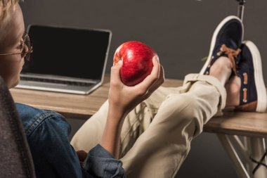 selective focus of little boy in eyeglasses holding apple and sitting with legs on table with laptop and lamp on grey background