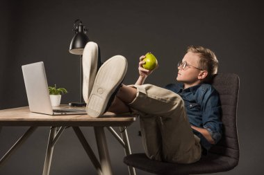 side view of little boy in eyeglasses holding pear and sitting with legs on table with laptop, plant and lamp on grey background