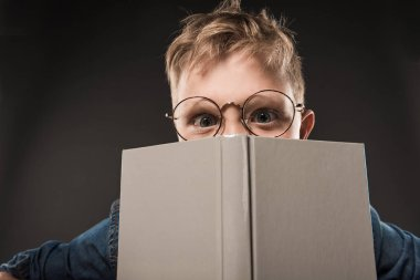 little schoolboy in eyeglasses covering face by book isolated on grey background