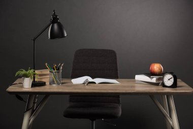 table with lamp, plant, books, colour pencils, eyeglasses, empty textbook, apple and clock on grey background