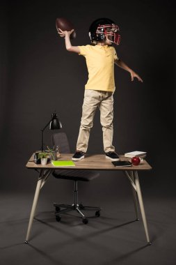 schoolboy in american football helmet throwing ball and standing on table with books, plant, lamp, colour pencils, apple, clock and textbook on grey background