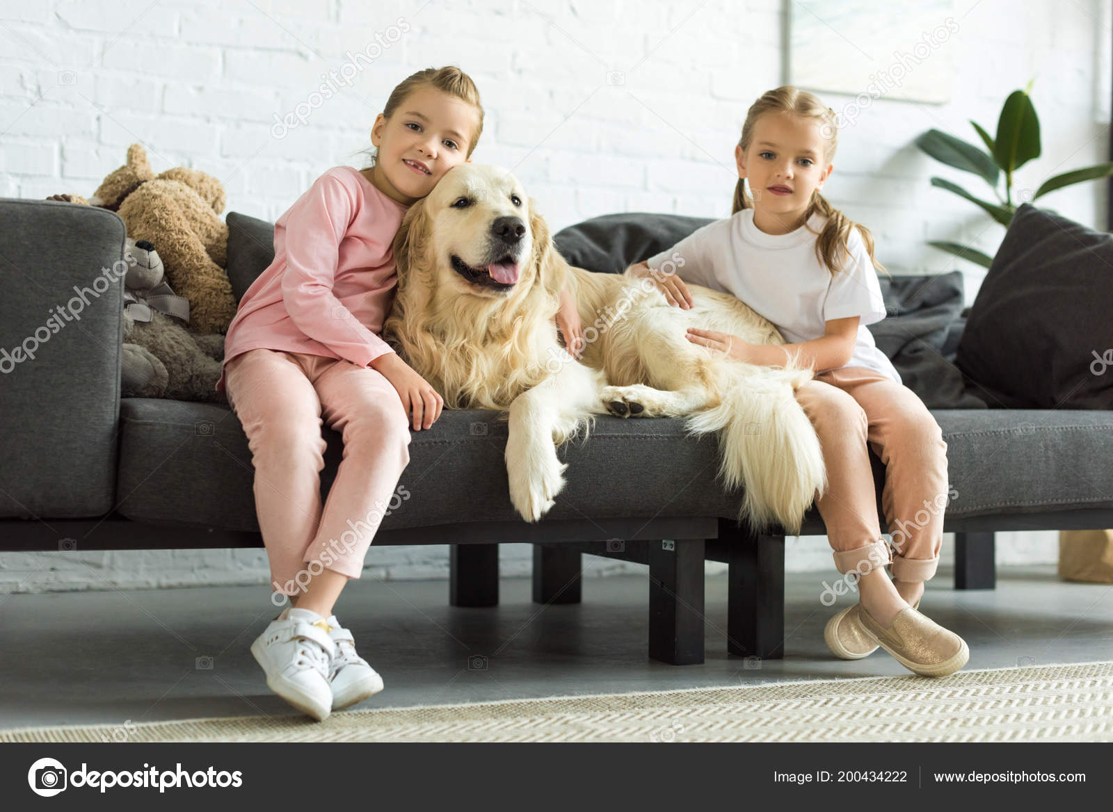 Adorable Kids Hugging Golden Retriever Dog While Sitting Sofa Home