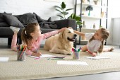 adorable kids petting golden retriever dog while drawing pictures on floor at home