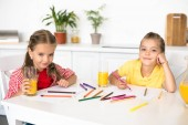 portrait of cute smiling little kids looking at camera while drawing pictures at table at home