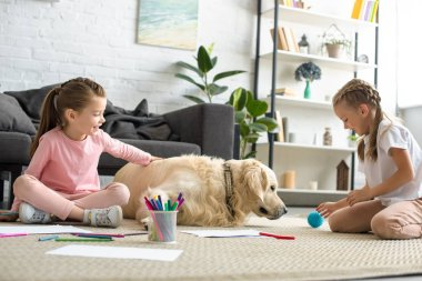 little children playing with golden retriever dog on floor at home