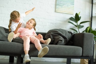 adorable little children having fun on sofa at home
