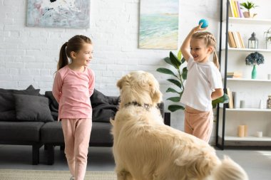 cute little children playing with golden retriever dog at home