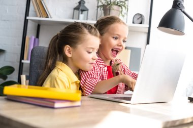 side view of cute little kids using laptop at table at home