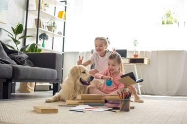 little sisters with books and golden retriever dog near by playing together at home