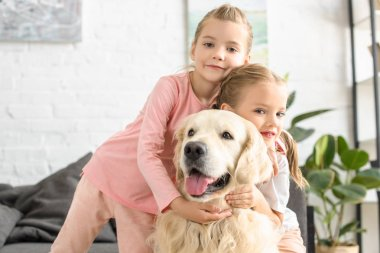 portrait of adorable kids hugging golden retriever dog at home
