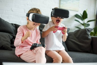 little kids in virtual reality headsets playing video game on sofa at home