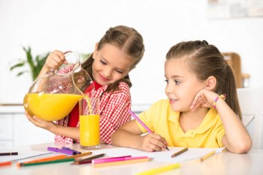 portrait of kid pouring juice into glass for sister at table with papers and pencils for drawing at home
