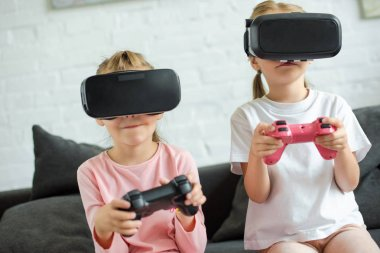 obscured view of kids in virtual reality headsets playing video game on sofa at home