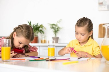 portrait of cute little kids drawing pictures at table at home