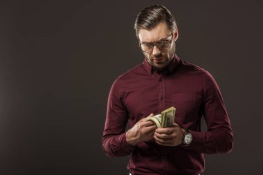 serious man in eyeglasses counting dollar banknotes isolated on black