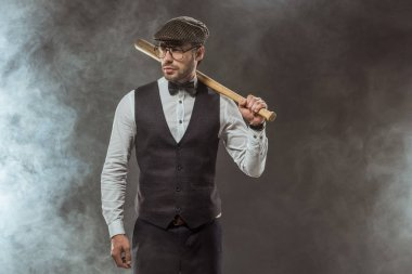 stylish man in bow tie, eyeglasses and cap holding baseball bat and looking away on black