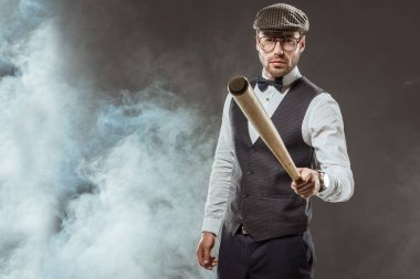 serious man in bow tie and cap holding baseball bat while standing in smoke