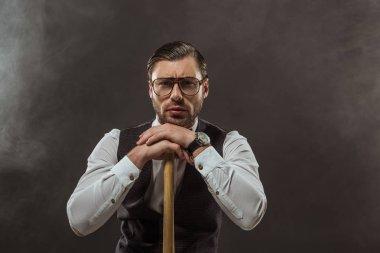 serious stylish man in eyeglasses leaning at baseball bat and looking at camera on black