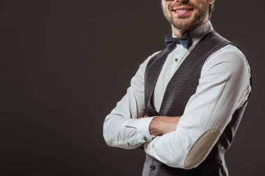 cropped shot of stylish smiling man in bow tie standing with crossed arms isolated on black