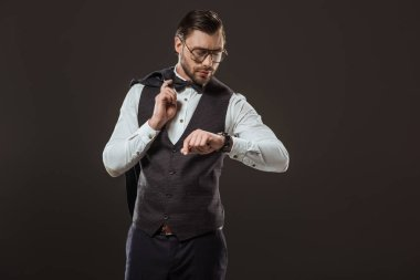 stylish businessman in bow tie and eyeglasses holding suit jacket and checking wristwatch isolated on black