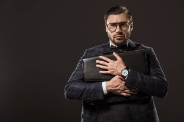 serious businessman in eyeglasses hugging briefcase and looking at camera isolated on black