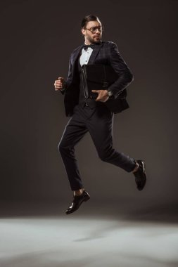 stylish businessman with briefcase jumping and looking away on black