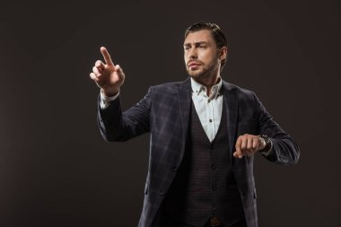 serious businessman checking wristwatch and pointing with finger isolated on black