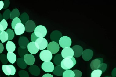 beautiful green shiny defocused bokeh on black background