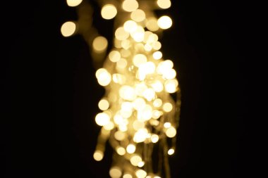beautiful shiny defocused golden bokeh on black background