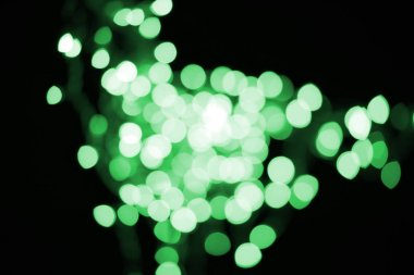 beautiful shiny defocused green bokeh on black background