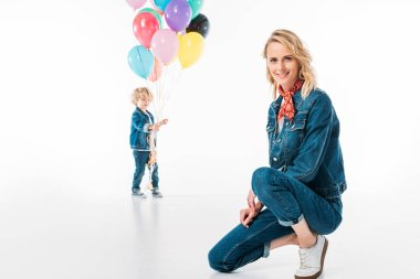 son walking with balloons and mother squatting on foreground on white